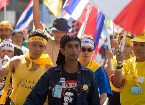 PAD Anti-Thaksin protesters walk on Bangkok street wearing yellow t-shirts
