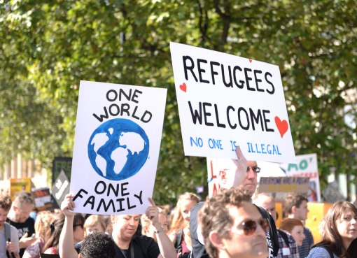 """Liberals holding banners reading """"One world - Refugees Welcome"""" during a pro-immigration demonstration in Europe"""