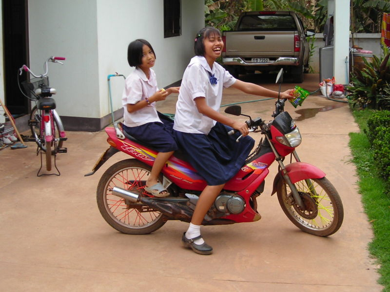 Young schoolgirls driving a motorcycle in Thailand