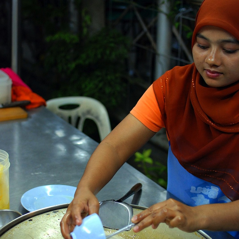 Muslim woman selling roti with banana and egg