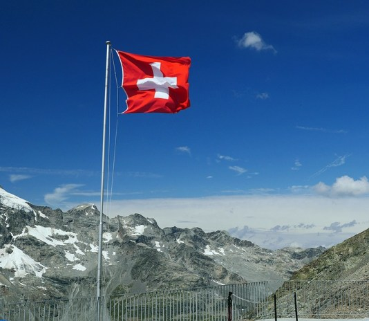 Switzerland National Flag and snowy mountains