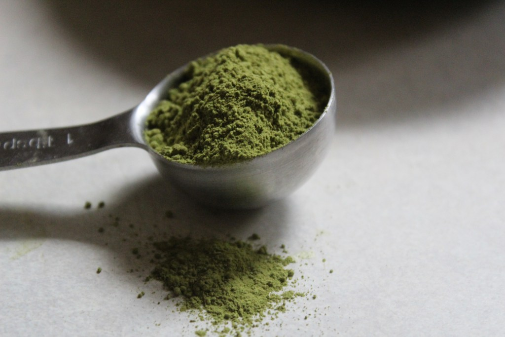 metal tablespoon with bright green powdered matcha