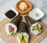 Salmon, tuna fish and Surimi avocado Temaki sushi with soy sauce, pickled ginger and wasabi on mat and marble background