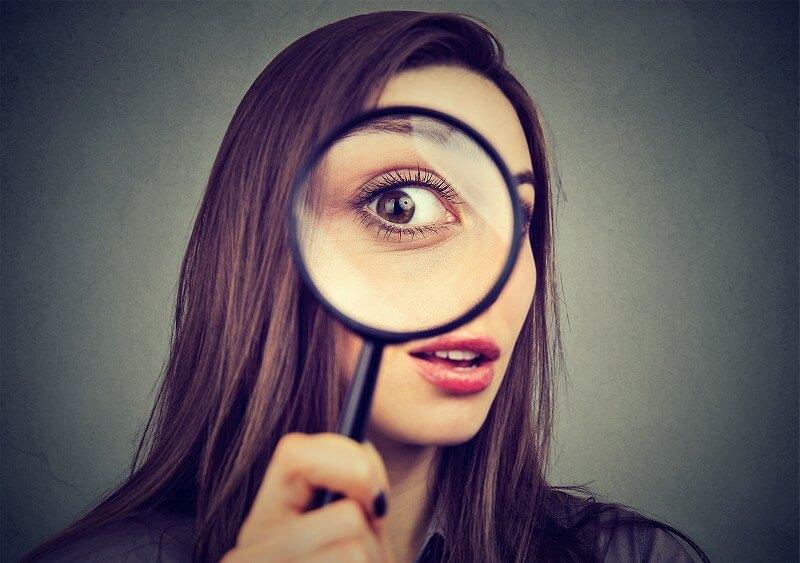 虫眼鏡を覗いている女性