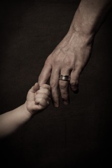 26733572 - child's small hand holding finger of his father, dark key