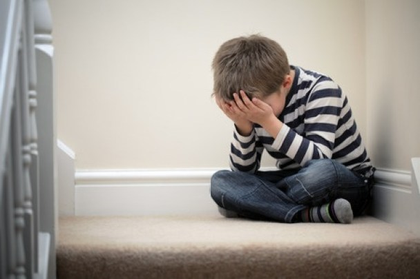 38970956 - upset problem child with head in hands sitting on staircase concept for bullying, depression stress or frustration
