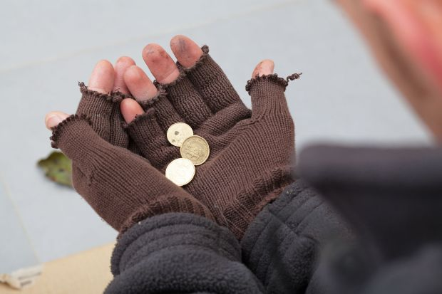 23049399 - homeless person holding a few cents in his hands