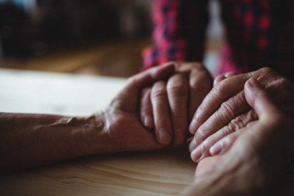 65488475 - close-up of senior couple holding hands at home
