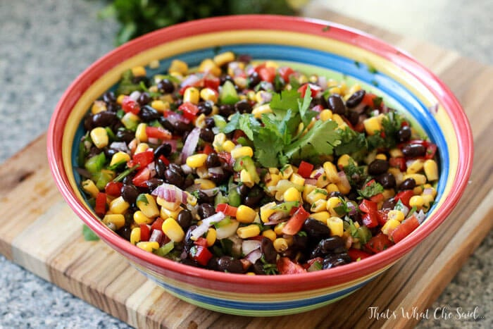 A colorful bowl filled with colorful Corn & Black Bean salsa with cilantro garnish