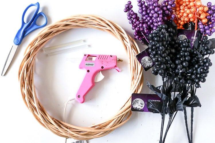 Wreath form, berry sprigs, hot glue gun and scissors