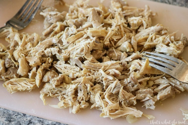 Chicken thighs that were cooked in the instant pot and now shredded on a cutting board with 2 forks.