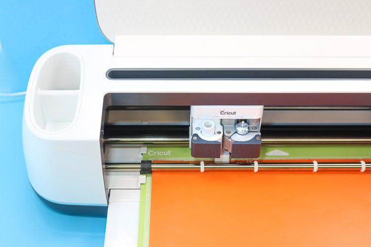 Cricut Maker Machine Loaded with Orange Vinyl on a Standard Green Mat