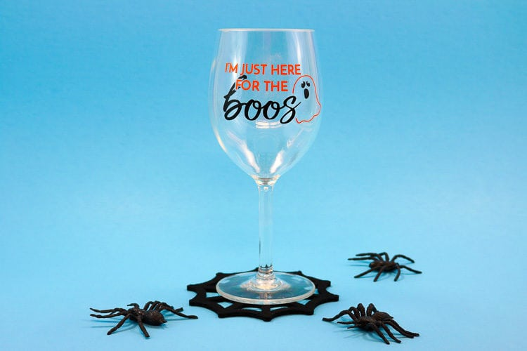 Wine glass with Halloween Vinyl and Spiderweb coaster with fake spiders