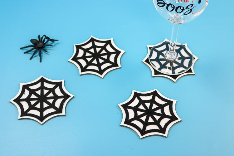 Coasters made with chipboard, vinyl and felt in the shape of spider webs