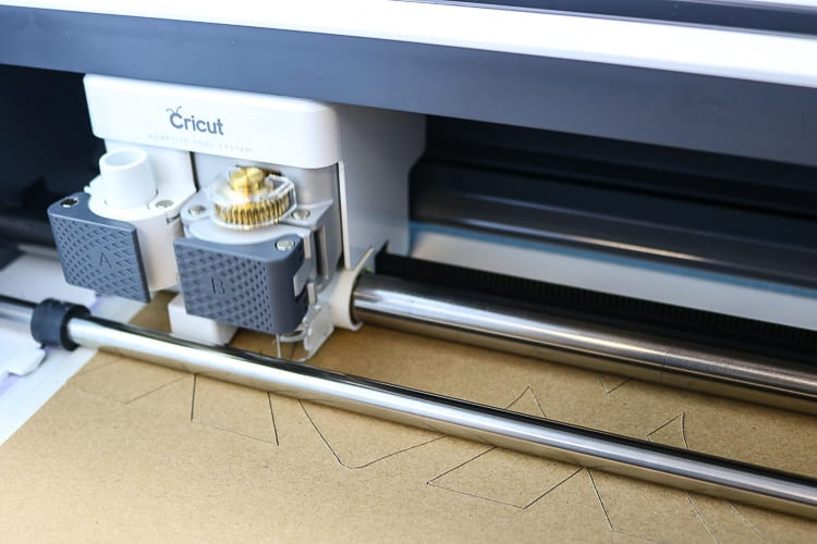 Close up view of the Cricut Maker cutting into Chipboard with the Knife Blade