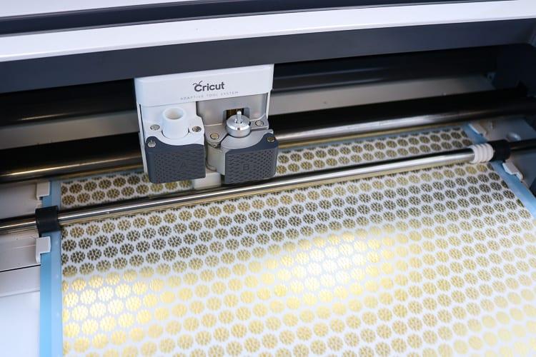 Cricut Maker with sheet of washi tape being cut on blue light grip mat.