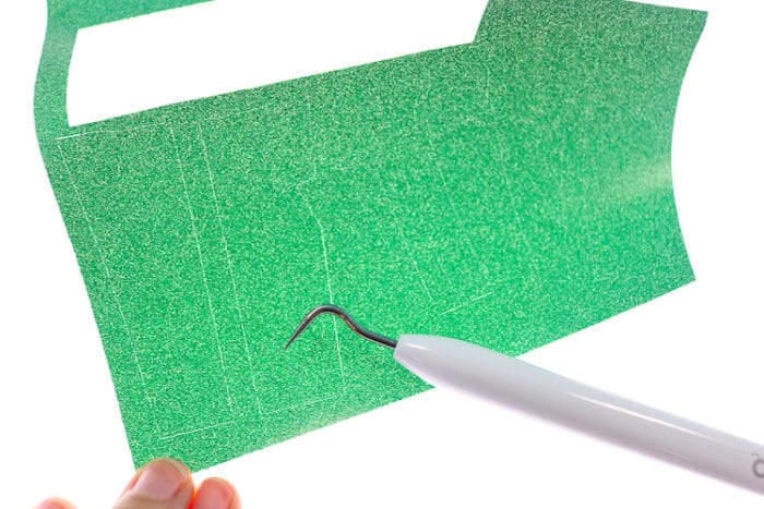 Close Up shot of how Bright Pad helps to see weeding lines on materials such as glitter iron on