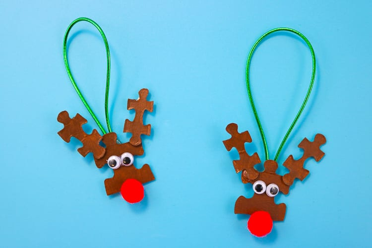 Two upcycled reindeer ornaments made from puzzle pieces and googly eyes and red pompoms