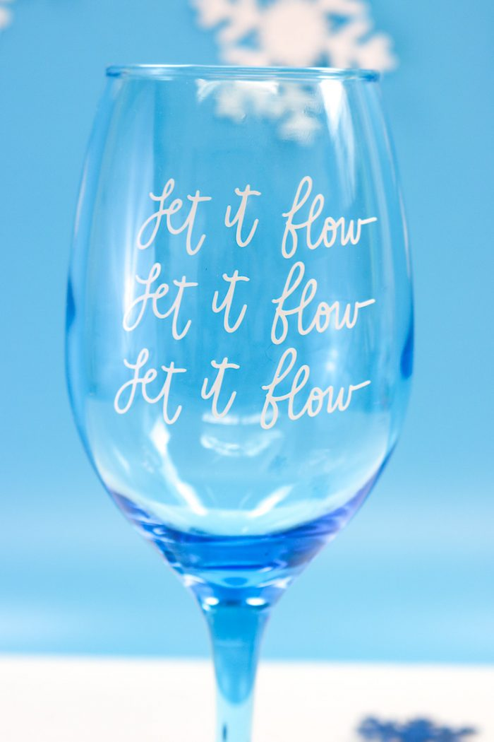 Closeup of Blue Wine Glass with Let it Flow, Let it Flow, Let it Flow in Vinyl