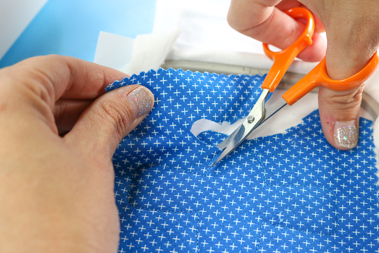 Cutting excess fabric away from applique stitching
