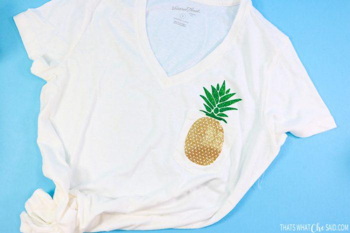White women's v-neck t-shirt with Pineapple base on pocket and stem on shirt
