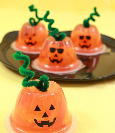 Orange fruit cups turned into jack-o-lanterns with faces and pipe cleaner stems