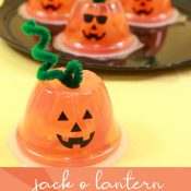 Orange fruit cups with vinyl jackolantern faces to make Halloween snacks