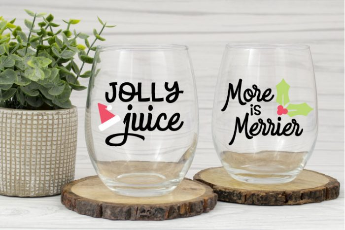 """Two clear stemless wine glasses with holiday SVG cut in adhesive vinyl.  One says """"Jolly Juice"""" and the other says """"More is Merrier"""""""
