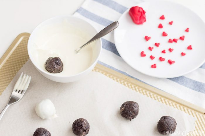 Truffles being dipped into a bowl of melted white chocolate.