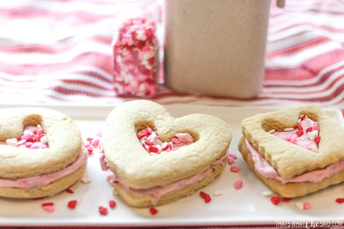 A long white plate with a heart circle and square shortbread sandwich cookie with heart centers