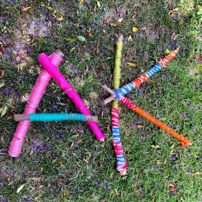 Large sticks wrapped in colorful yarn in shape of letters.