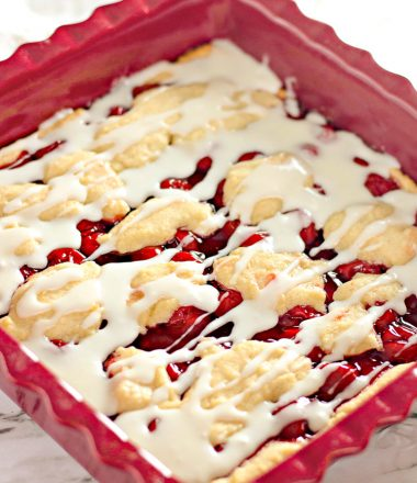 Homemade Cherry Bars in Baking Dish with frosting drizzle - Vertical Shot