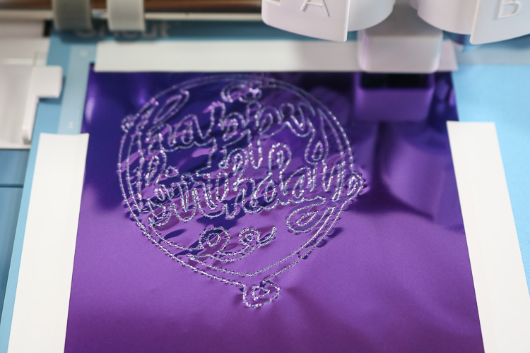 Close up of purple foil that has been pressed onto cardstock in the design of a happy birthday balloon