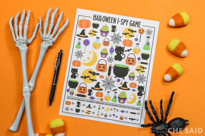 Orange background with Halloween I-spy printable and a pen and halloween decorations around it - horizontal orientation