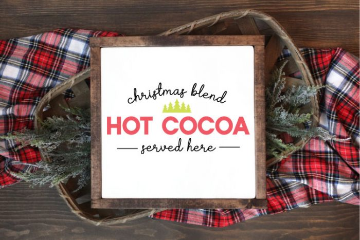 """Square sign with white background and wooden frame laying one a basket of evergreens snips and a plaid fabric.  """"Christmas Blend Hot Cocoa Served here"""" is applied in vinyl"""