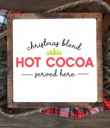 """Square sign with white background and wooden frame laying one a basket of evergreens snips and a plaid fabric. """"Christmas Blend Hot Cocoa Served here"""" is applied in vinyl - vertical"""