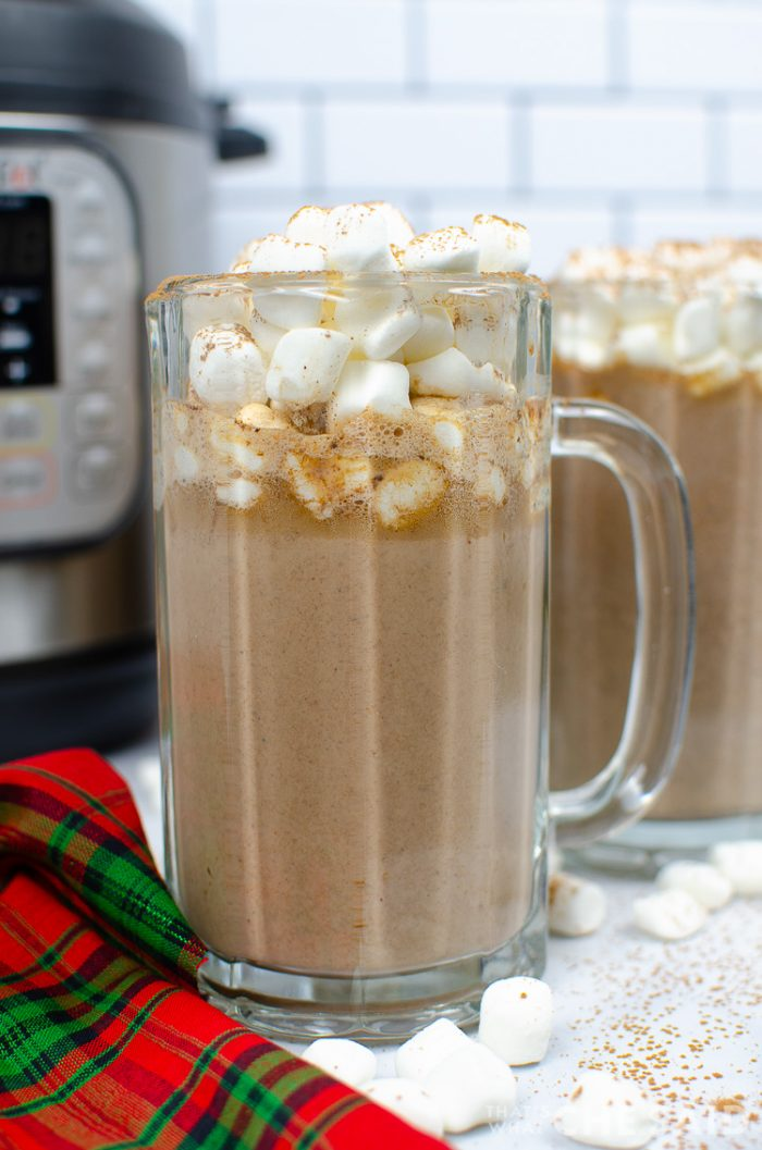 Tuxedo Hot Chocolate in a tall glass mug with marshmallows on top. Another mug and Instant pot is in the background
