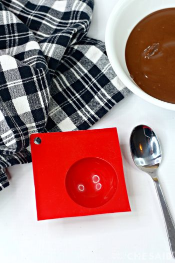 Bowl of melted chocolate and half sphere silicone mold and spoon
