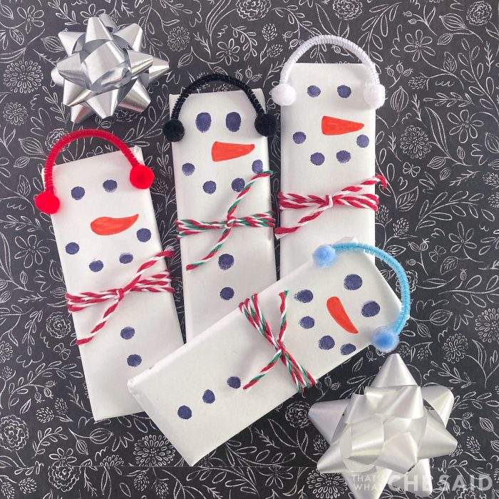 4 snowman candy bars on black background with bows square format
