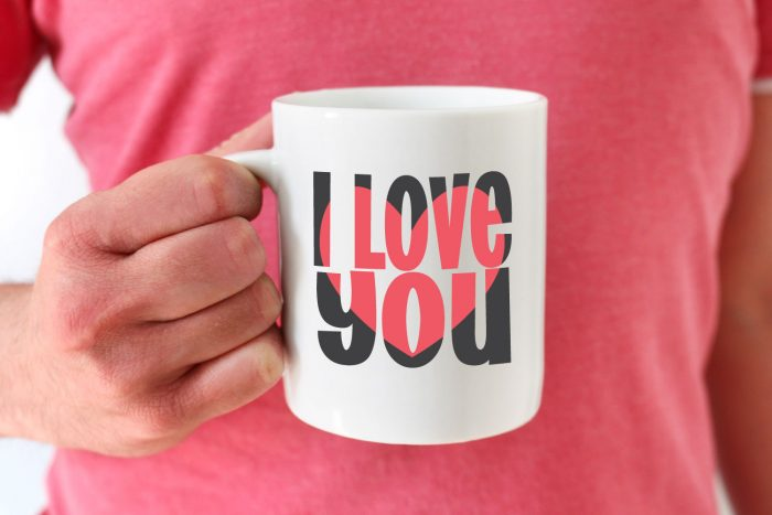 two tone block out i love you svg design on a white mug held by a man in pink shirt