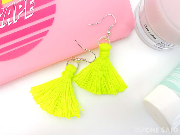 Completed bright yellow tassel earrings amongst some make up products