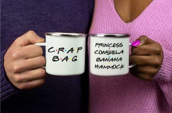 """A man and woman holding white coffee mugs with """"Crap Bag"""" and """"Princess Consuela Banana Hammock"""" in vinyl in the FRIENDS show font."""