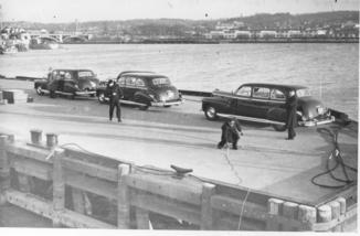 Autos line the pier awaiting the return of President Truman to Washington on a voyage on the USS Williamsburg.