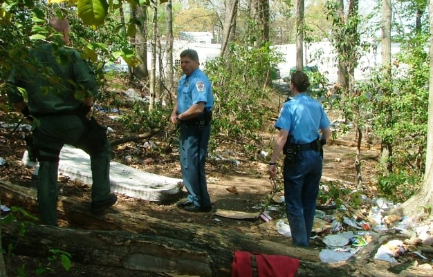 St. Mary's County Md. Sheriff Tim Cameron with Capt. Steve Hall and deputy in Hobo camp next to the Lexington Park library.  Much of this camp has been cleared away but evidence of lingering hobos in nearby woods remains. THE CHESAPEAKE TODAY photo