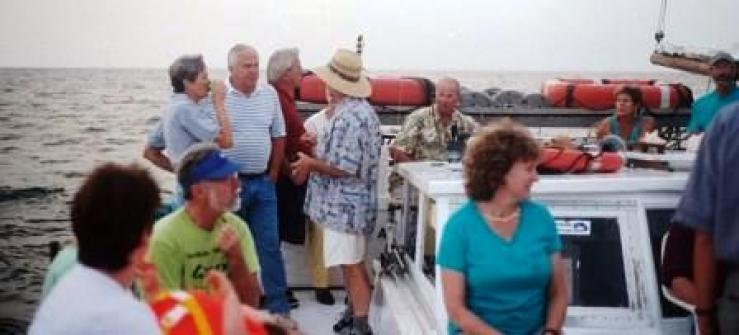 Francis Jack Russell at the helm of his Skipjack Dee of St. Mary's with enviro-tourists learning about saving the Chesapeake Bay.