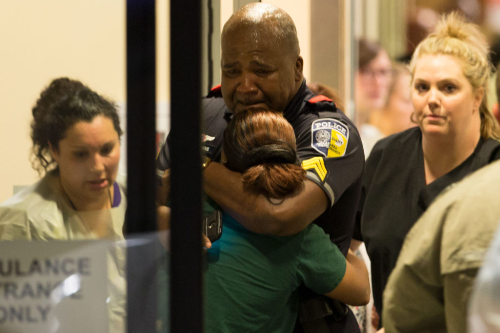A Dallas Area Rapid Transit police officer is comforted by another officer after massacre of five officers in Dallas Photo AP
