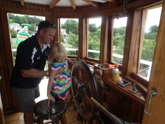 The present owner and master of the Iva W., Scott, hosts a family  for a tour of the pilot house and even the engine room of the ship. The Iva W has had three engines in its lifetime, with the Caterpillar 13000 diesel engine which was installed about the end of WWII. THE CHESAPEAKE TODAY photo