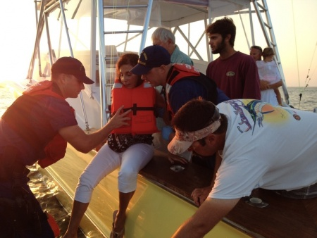 Crew from Station Chincoteague assist a wounded woman onto their 24-foot Special Purpose Craft. The pleasure craft CHASER ran aground during the 2015 Chincoteague Pony Swim with six adults on board and two children.