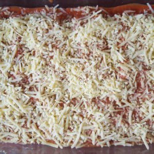 Die gefüllten mit Tomatensoße übergossenen Cannelloni mit geriebenen veganem Käse bestreuen und ab in den Ofen