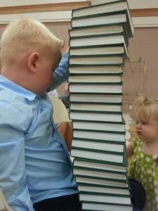 kids stacking hymnbooks in church